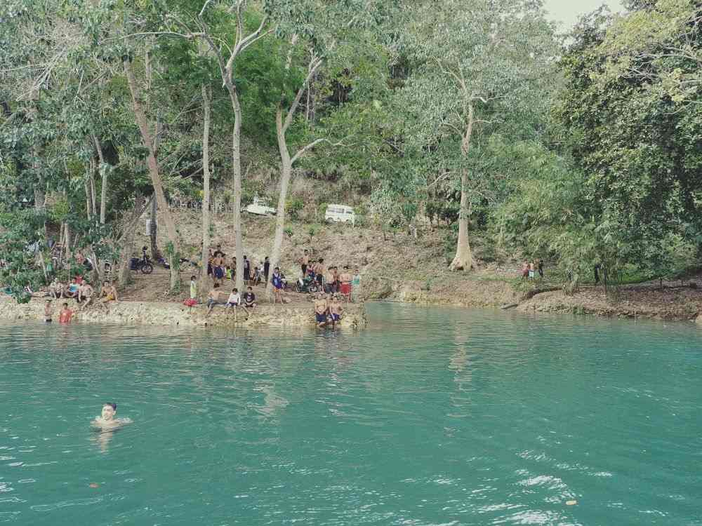 People swimming along the banks of Loboc River