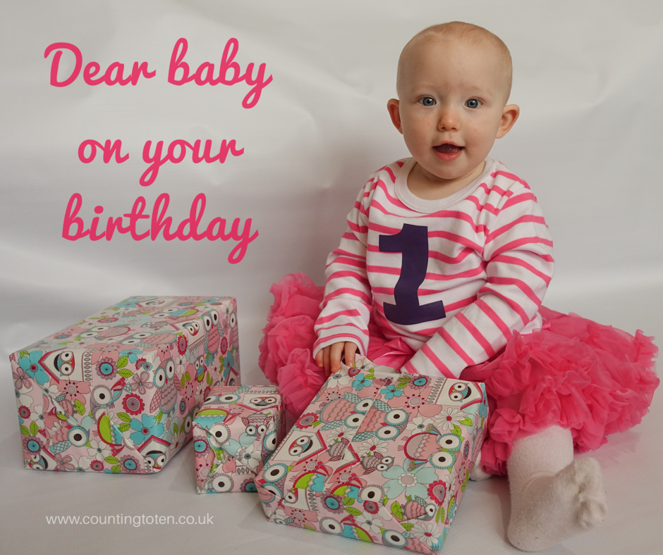 "Text saying ""dear baby on your birthday"" with a picture of a one year old girl with short hair in a white and pick striped t-shirt and a purple one, and a pink tutu, sitting next to a pile of presents."
