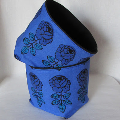 two royal blue fabric baskets with large flowers; black interior