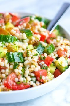 We love this light couscous salad — it doubles as a side, can be the main event or works well topped with grilled chicken or Adam's favorite, shrimp! With lots of texture from crisp cucumber, sweet tomatoes, crunchy nuts and raisins, this is certainly one of our favorites. You can even make it ahead of time. See the notes section below for our tips.