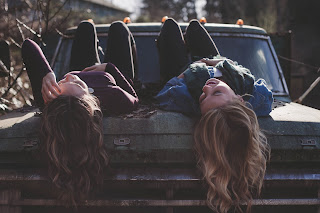 two girls with long hair dangling over car hood