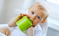 ребенок пьет из зеленой чашки-непроливайки