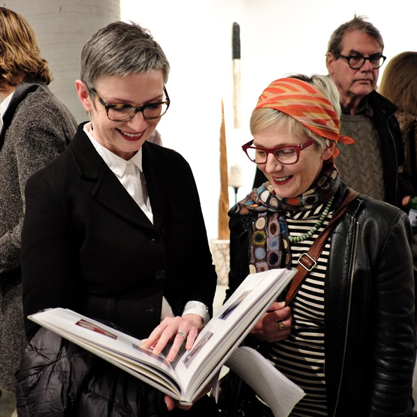 Two stylish women view a catalogue at Liverpool Street Gallery. Black Jackets, Orange headscarf. at Street Fashion Sydney - Photographed by Kent Johnson.