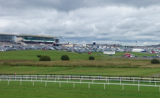 Photograph of a racecourse from a distance, with the grandstand on the left hand side