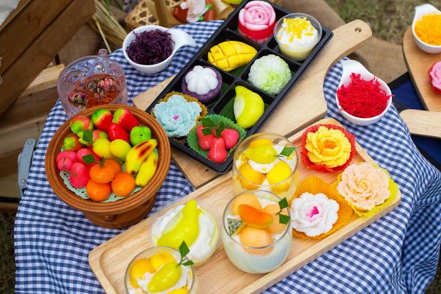Cụ thể, dạo một vòng quanh vài khu chợ, bạn sẽ thấy hầu hết các bánh ngọt đều có khoảng 5 - 6 màu sắc khác nhau, bao gồm hồng, xanh lá, vàng, tím, xanh dương... Trong đó xanh dương là một điểm độc đáo mà gần như không ẩm thực nơi đâu có.