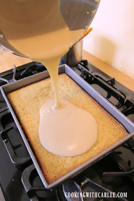 pouring caramel frosting over banana cake