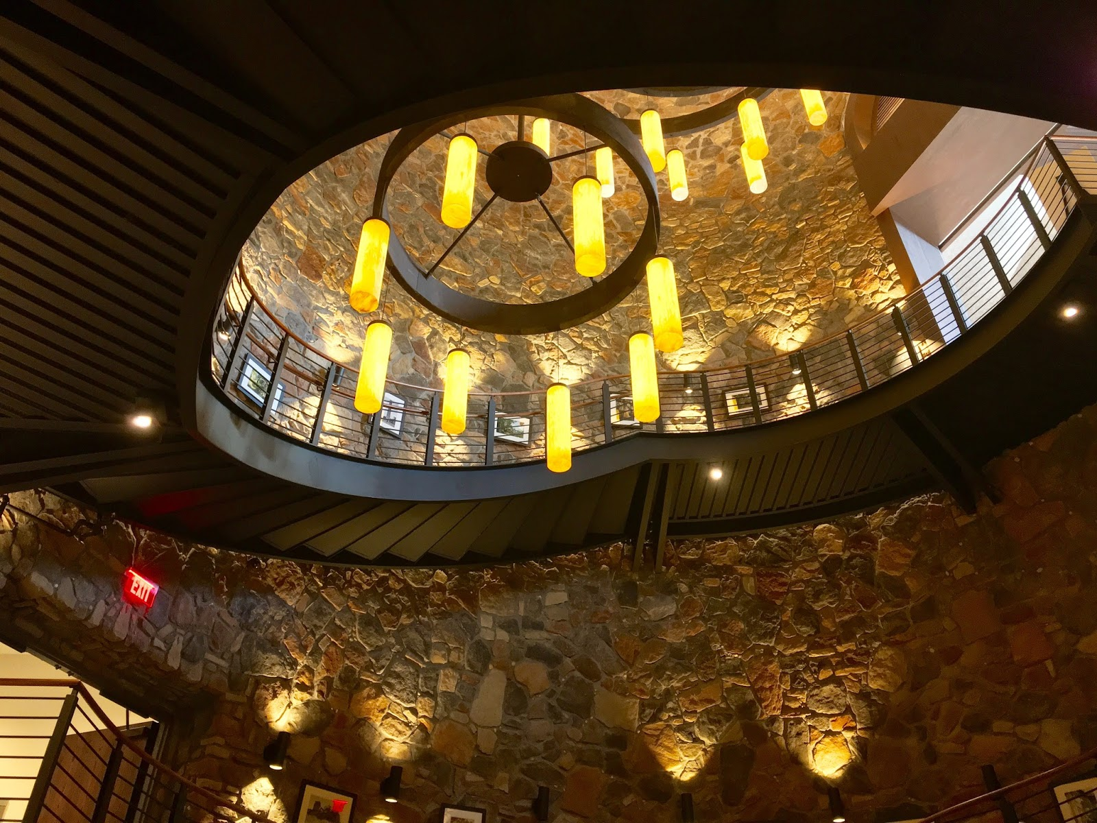 Epic Detailing on this spiral staircase is amazing from the beautifully crafted staircase to the expansive stone rock work and massive hanging light fixtures