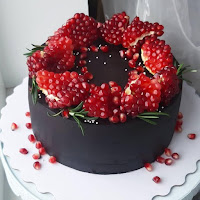black cake with pomegranate topping on a white plate - wedding ideas - wedding planning services by K'Mich Weddings in Philadelphia PA