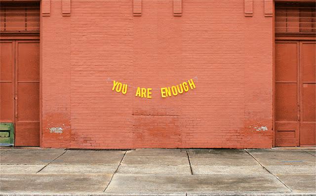 photographie artistique d'un mur de brique rouge avec un message d'amour