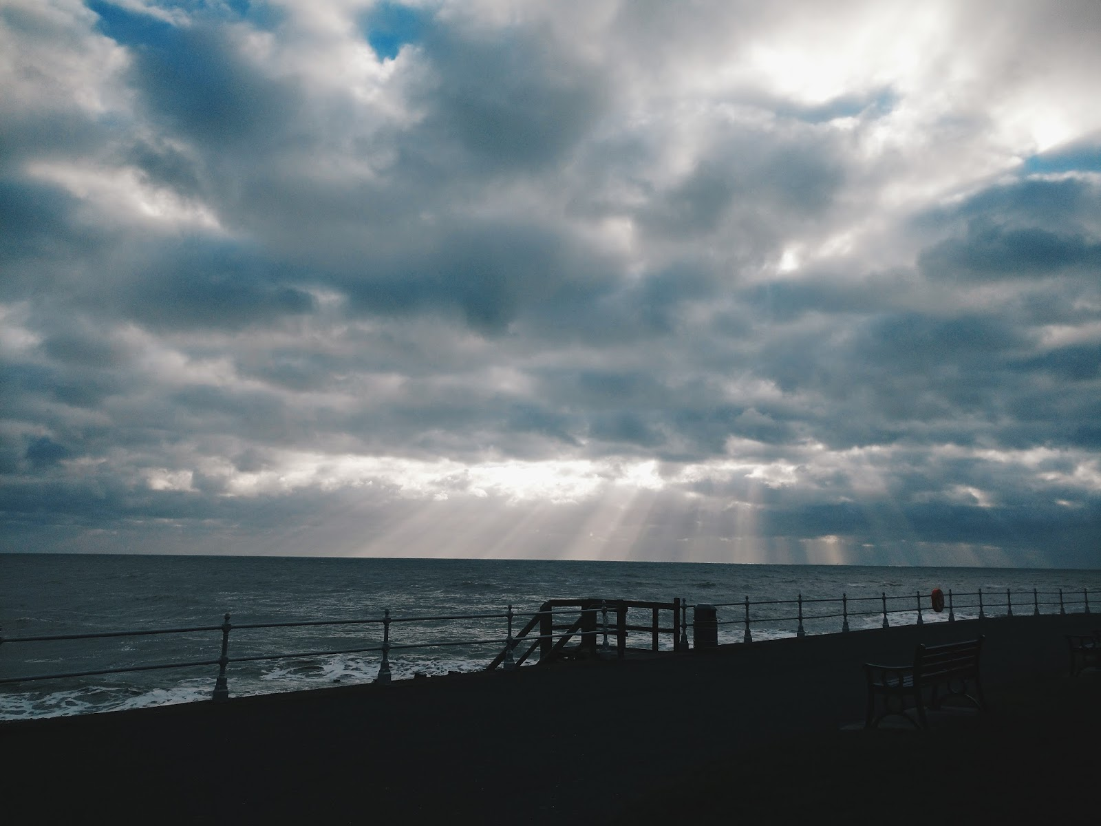 sun shining through the clouds at the beach