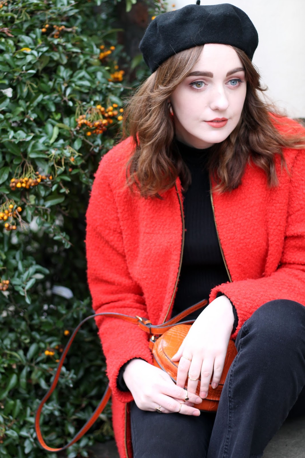 UK style blogger models black beret, blood orange coat, orange round bag and black jeans