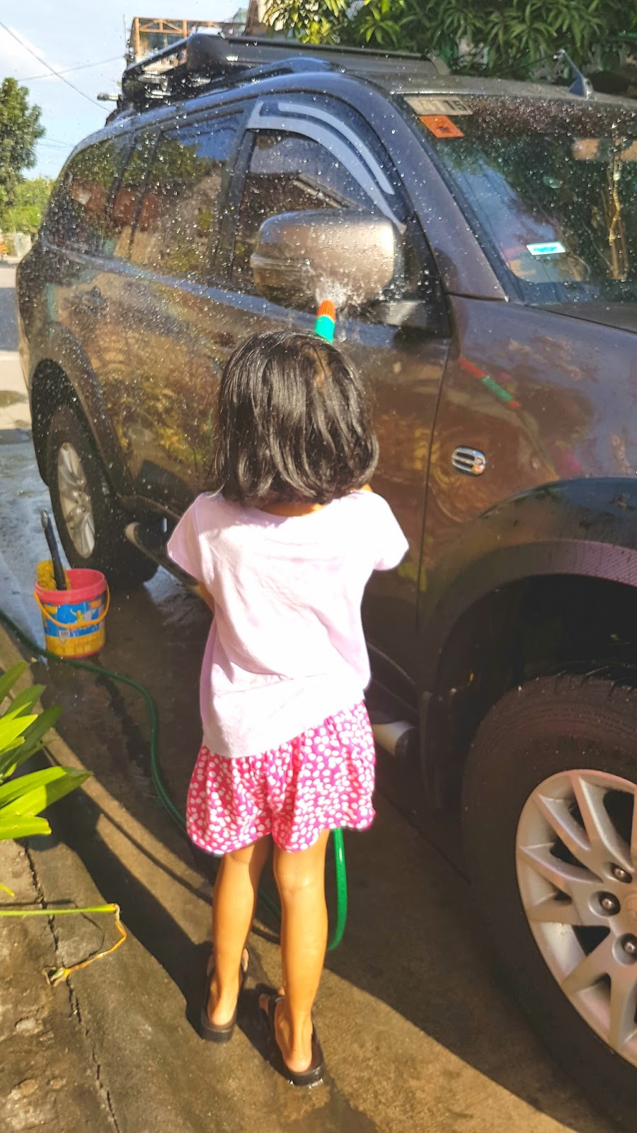 kid car washing an suv called mitsubishi montero outside the house