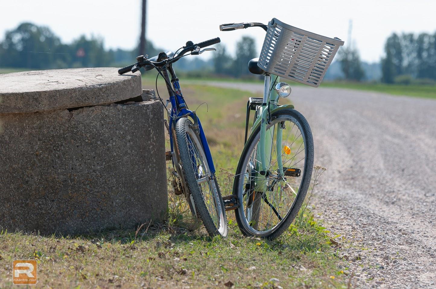 Divi velosipēdi stāv ceļa malā