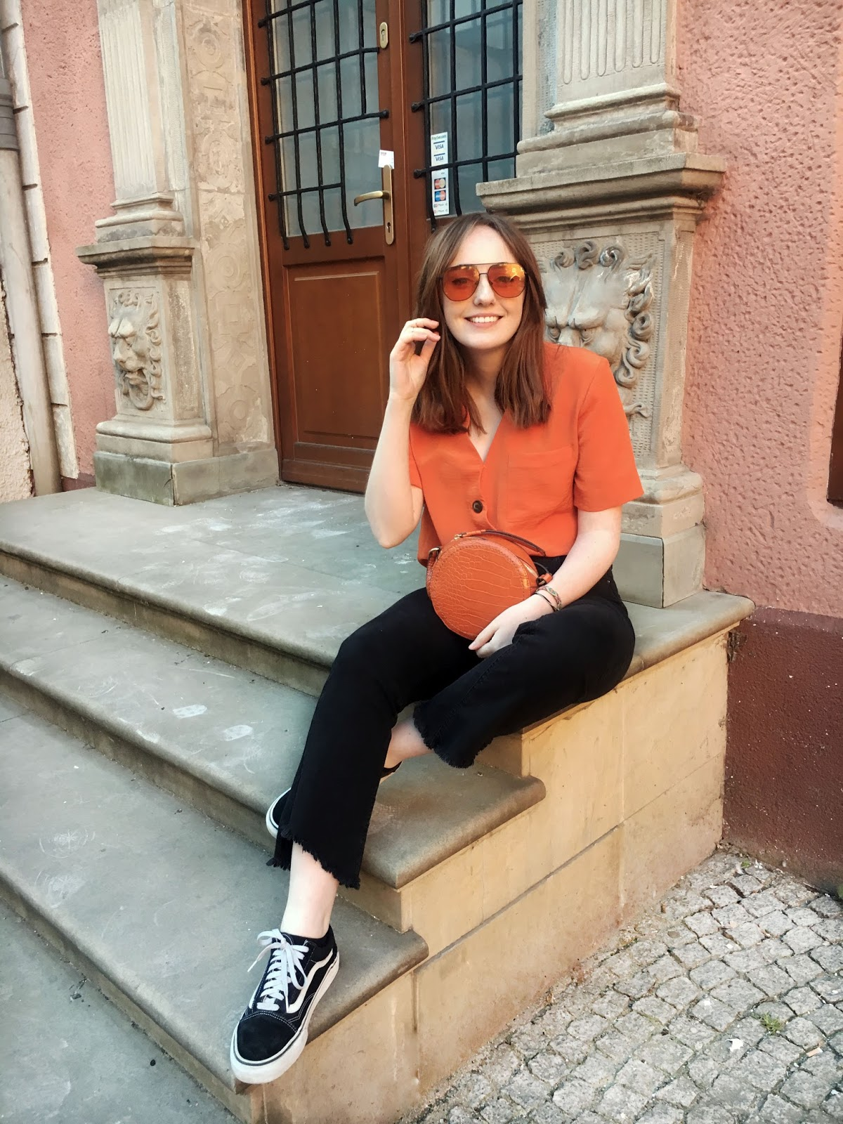 fashion blogger wearing burned orange button down blouse, orange tint aviator sunglasses, black crop kick flare jeans and old skool vans