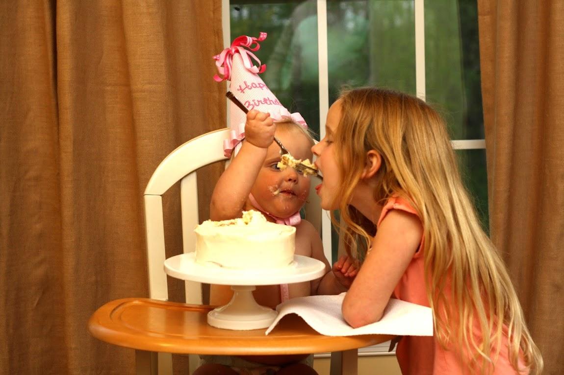little girl eating cake in high chair