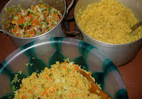 Cooked fried rice being mixed with vegetables in a bowl