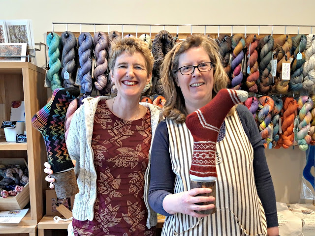 Christine Perry (Winwick Mum) and Carrie Warr both smiling and holding up hand knitted socks.