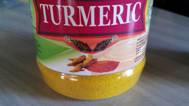 A brightly colored turmeric powder in a bottle