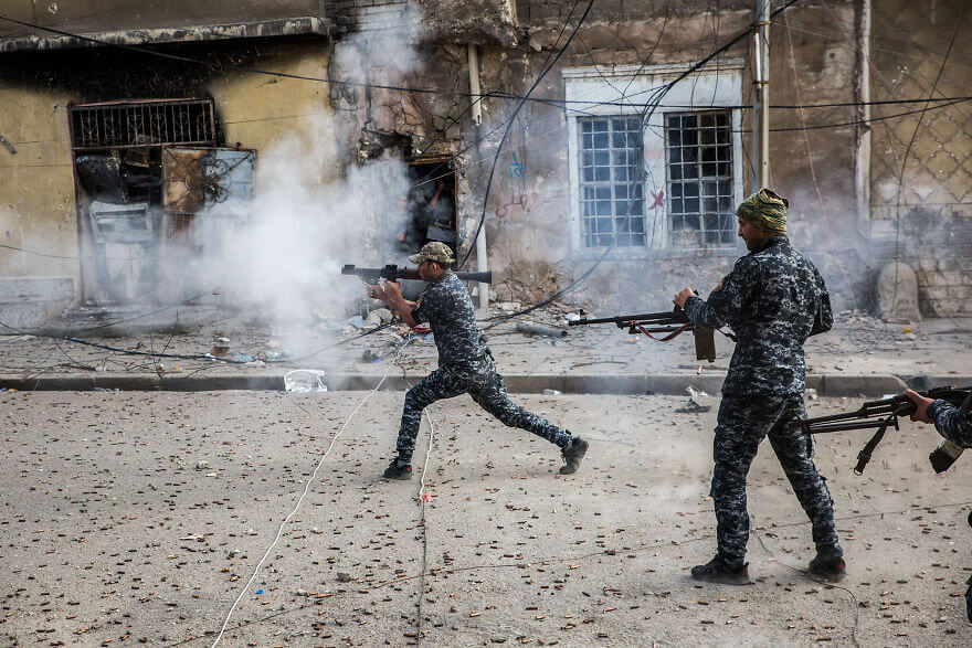 Powerful Heart-Breaking Pictures Of The Battle Of Mosul - Federal Police fire at Islamic State positions at the end of the street in the Old City