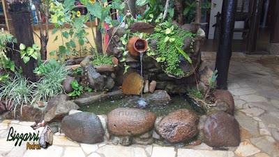 Detalhe do laguinho de carpas com pedra do rio com a bica d'água no pote de barro com a execução do paisagismo e o piso de pedra com cacos de São Tomé.