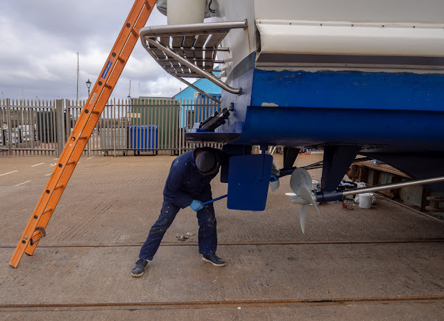 Photo of Phil applying antifouling paint with a roller