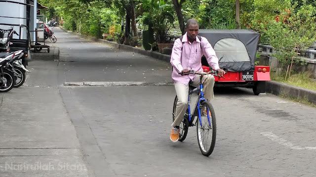 Seorang mahasiswa internasional sedang berangkat ke kampus menaiki sepeda