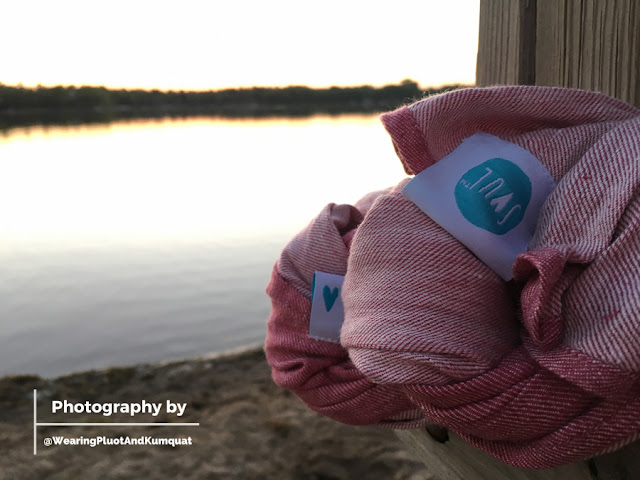 [Image of a pinkish reddish linen woven wrap named Cardinal braided with the blue heart middle marker and blue SOUL logo tags visible against the backdrop of a sun that has set into a calm lake.]