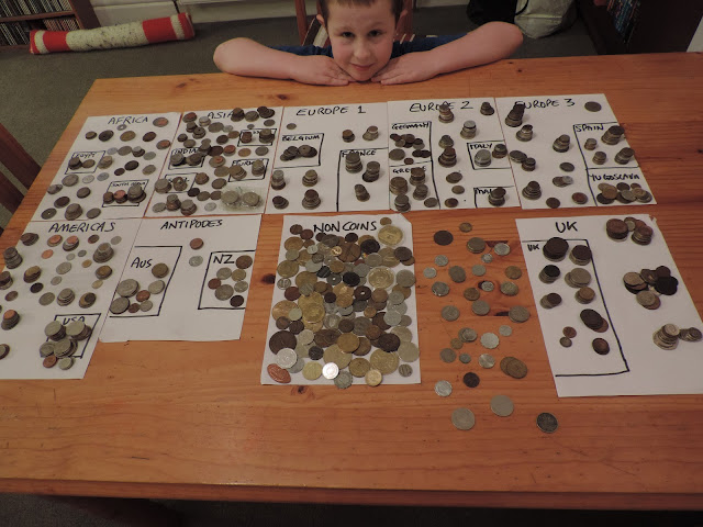 piles of assorted coins split into continents