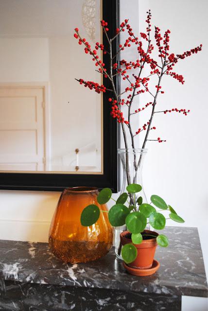 Op een marmeren mantel staat een okergeel glazen vaasje, een doorzichtige vaas met takken en een klein Pilea plantje.
