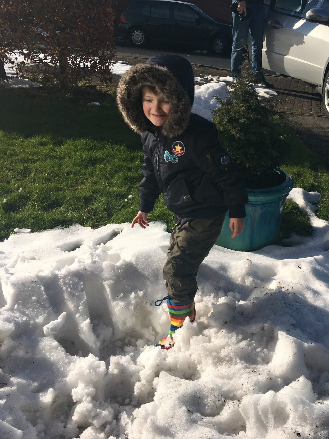 boy-jumping-in-snow-wearing-rainbow-wellies-and-facing-the-camera