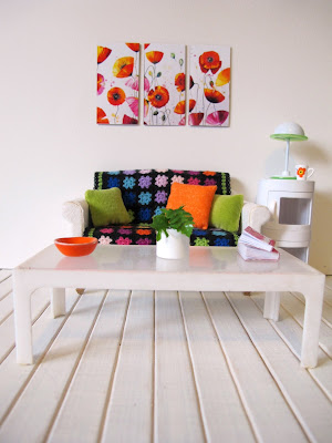 Modern dolls' house miniature lounge in white with a rainbow crocheted afghan rug on the sofa and bright poppy art on the wall.
