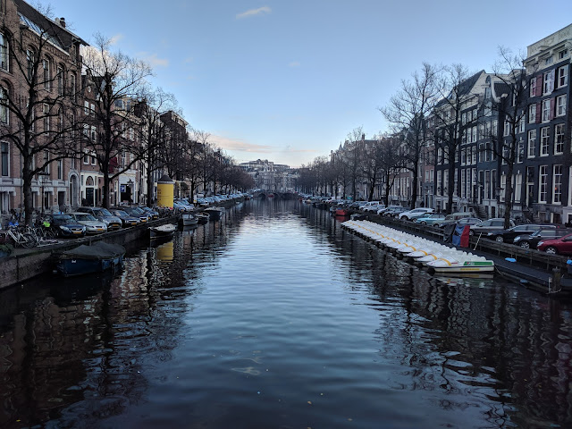 Amsterdam canal with small boats, during day time