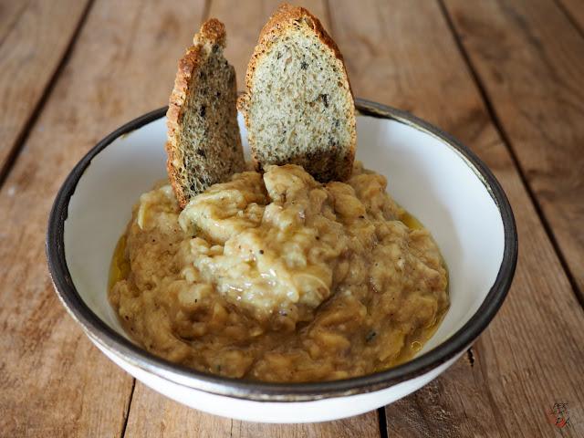 Paté de berenejenas ahumadas, asadas directamente en las brasas y aderezadas con ajo, yogur, azúcar, limón, melaza de granada, zumaque y aceite de oliva.