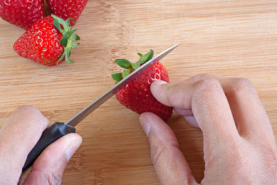 Slicing off the strawberry tops