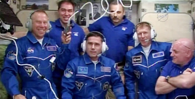 The six-member expedition 46 crew gathers for a ceremony in the Zvezda service module as friends and family congratulate the new arrivals. From left are Flight Engineers Tim Kopra, Sergey Volkov, Yuri Malenchenko, Mikhail Kornienko and Tim Peake with Commander Scott Kelly. Credit: NASA TV
