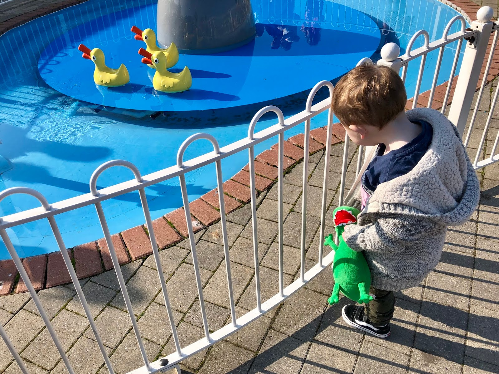 toddler boy holding toy dinosaur and looking at ducks at peppa pig world paultons park