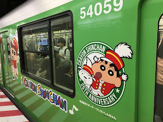 A green Tokyo subway train plastered with pictures of Crayon Shin-Chan to celebrate the 25th anniversary of the anime