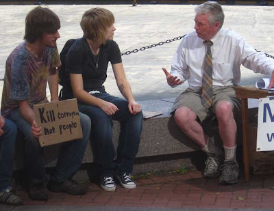 Two young guys talking to a guy in a tie, one young guy with small sign that says Kill corruption not people