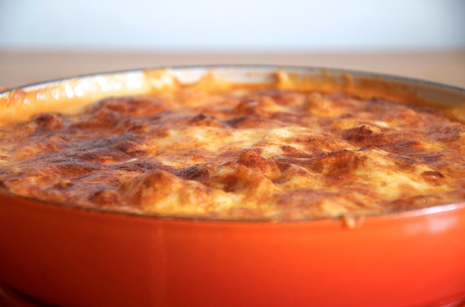 orange cast iron casserole with cheesy buffalo chicken dip