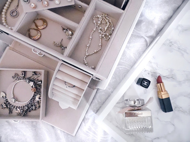 flatlay of jewellery box filled with jewellery next to a tray with perfume and lipstick on it