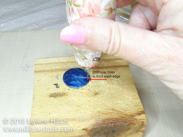 Using the drill to drill a hole in the resin disk.