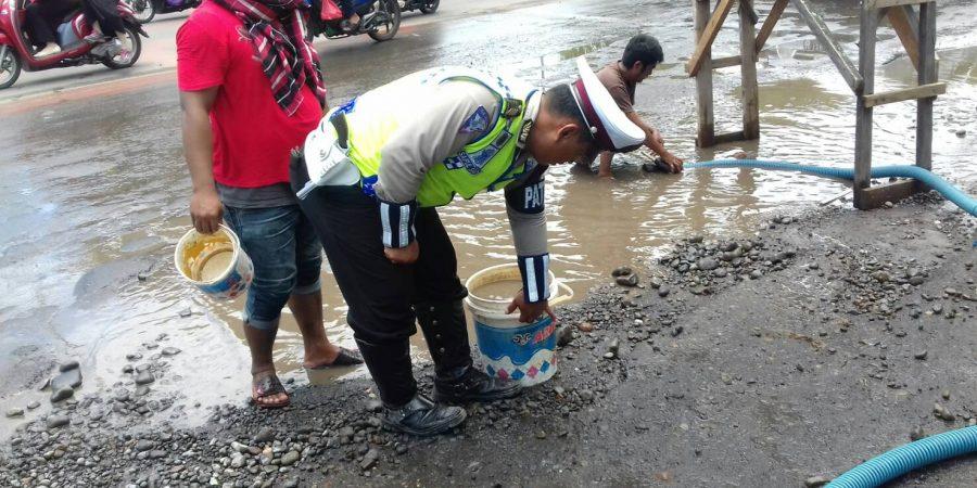 Polantas Gowa Bantu Masyarakat Kuras Air yang Tergenang di Badan Jalan.