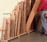 wood planks being organized vertically by a man on red shirt and blue jeans.