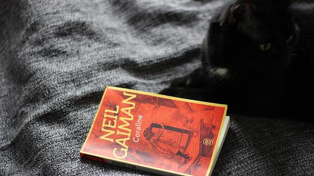 Livre Coraline de Neil Gaiman et un chat noir