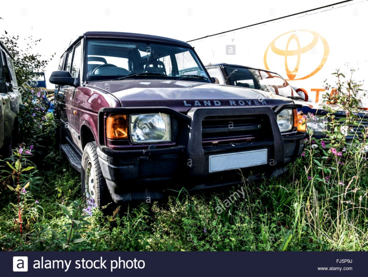An old 4 x 4 Landrover left to rot in a field where parts have