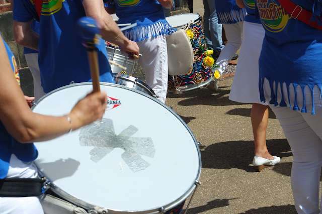 a drummer beating a bass drum in a crowd