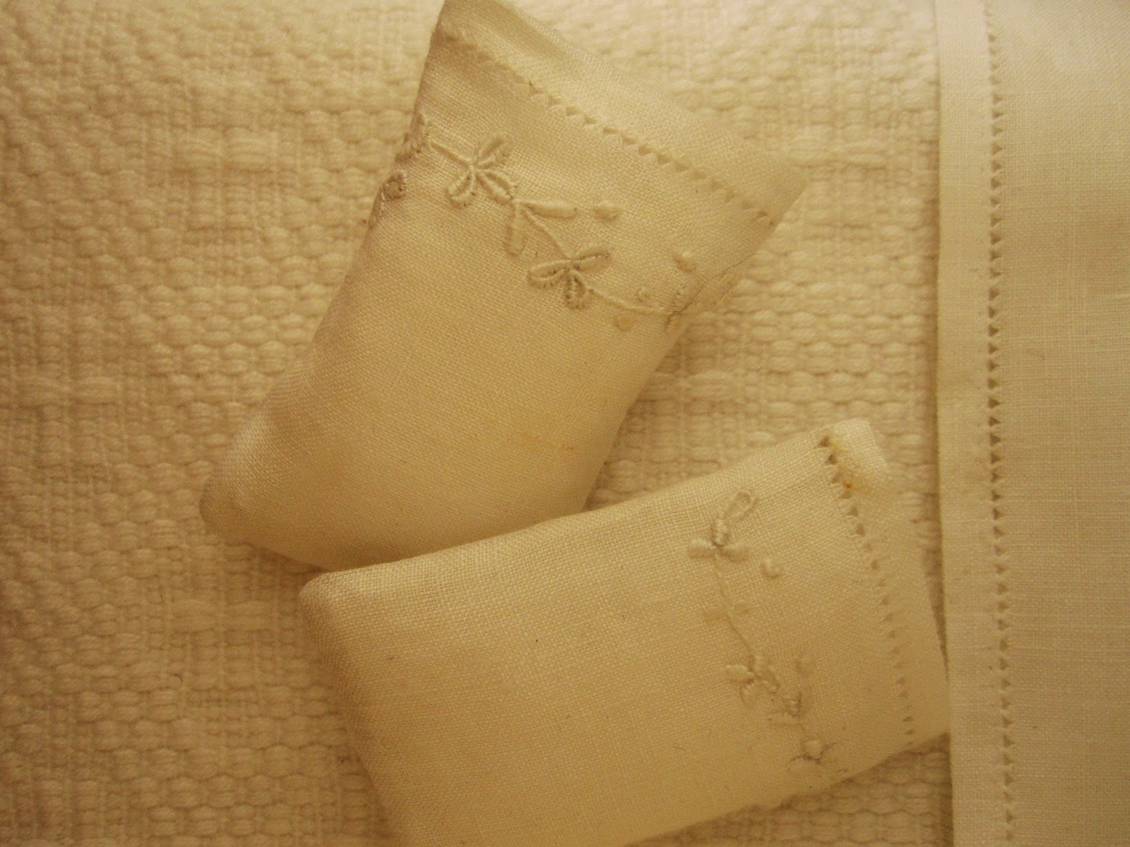 Two dolls' house miniature embroidered pillow cases on pillows, displayed on a white cotton bedspread.