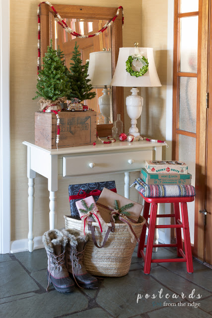 entry with white desk and red stool with farmhouse Christmas decor