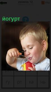 маленький мальчик ложкой ест йогурт ложкой из стаканчика