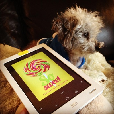 Murchie lays on his sheep-shaped pillow with his head raised. He wears a blue hoodie with white trim. Beside him is a white Kobo with So Sweet's yellow cover on its screen. The cover features a large lollipop in red, yellow, pink, and green swirls.